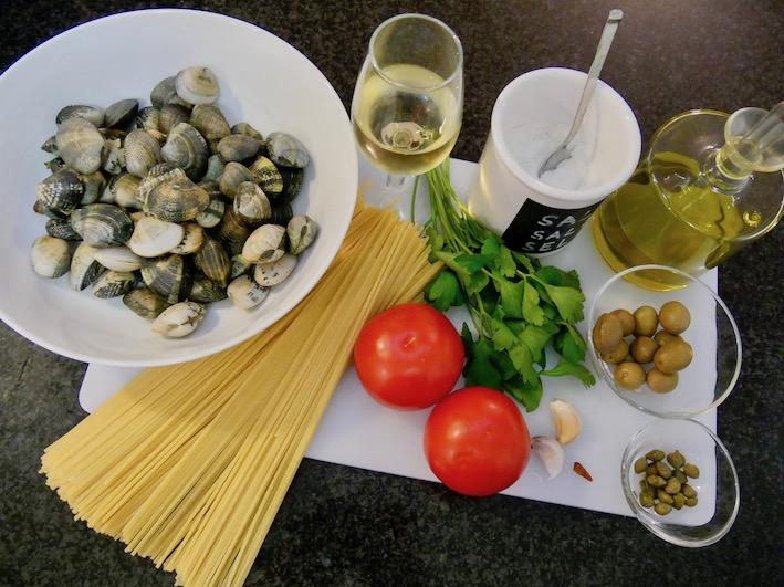Die Zutaten für die Spaghetti all'algherese mit Vongole, Tomaten, Oliven und Kapern